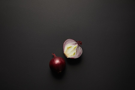 Top view of fresh cut onion on black surface