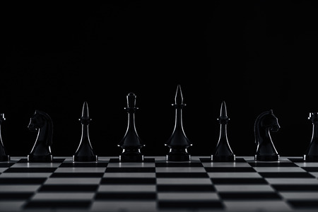 chessboard with black chess figures isolated on black