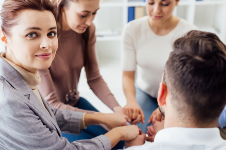 group of people stacking hands during therapy session
