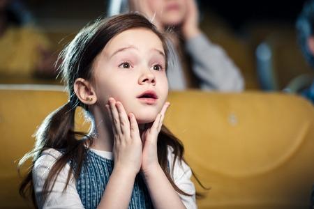 selective focus of cute worried child watching movie in cinema Foto de archivo
