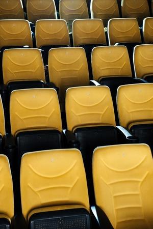 rows of empty orange comfortable seats in cinema hall