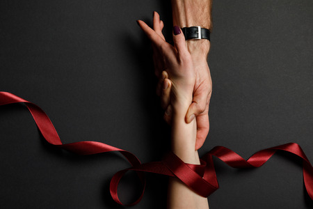 cropped view of man holding female hand in red satin ribbon on black background