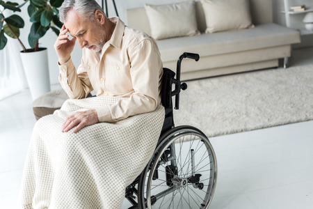 pensive disabled senior man sitting in wheelchair at home