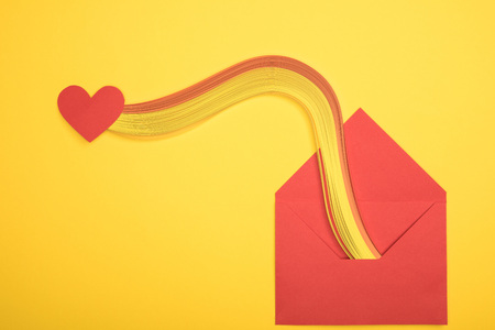 top view of open red envelope with rainbow and heart sign on yellow background