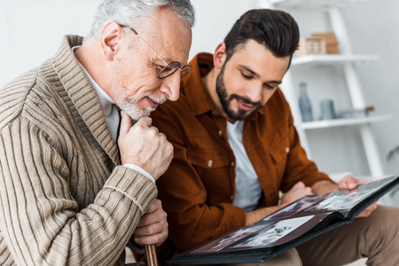 handsome bearded man and senior father in glasses looking at photo album
