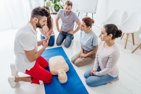 handsome instructor gesturing during first aid training with group of people