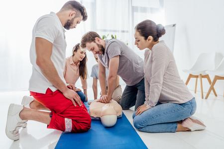 groupe de personnes regardant l'homme effectuant la RCR sur mannequin pendant la formation aux premiers secours Banque d'images