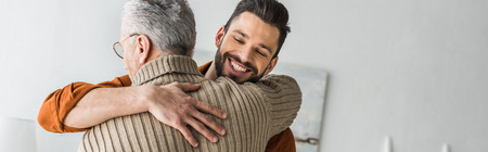 panoramic shot of happy bearded man smiling while hugging elder father at home