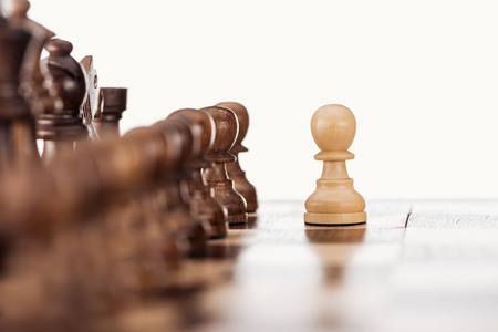 selective focus of wooden chessboard with chess figures and pawn in front isolated on white Stock Photo