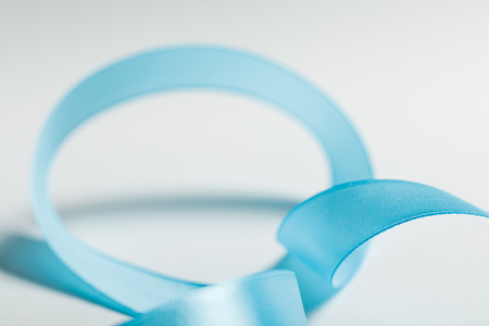 close up of curved blue satin ribbon on grey background Фото со стока