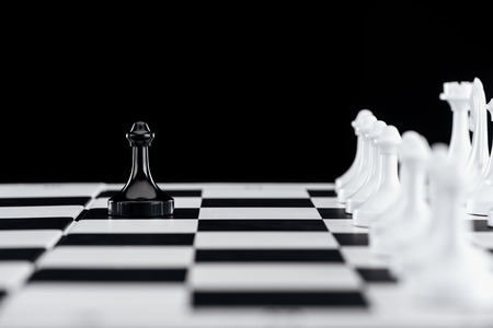 selective focus of chessboard with white chess figures and black pawn in front isolated on black