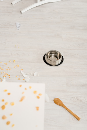 selective focus of metal bowl, wooden spoon and broken dishes on floor in kitchen