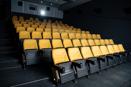 dark cinema hall with comfortable empty seats with cup holders