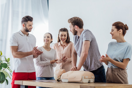 group of people applauding while man performing cpr on dummy during first aid training Stock Photo