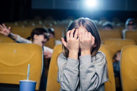frightened child holding hands on face while watching movie in cinema