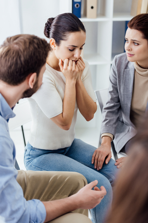 selective focus of worried woman covering mouth with hands during group therapy session
