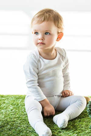adorable baby with blonde hair sitting on green grass and looking away on white
