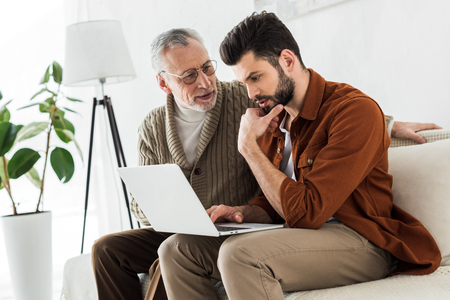senior father looking at handsome son sitting with laptop