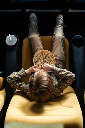 overhead view of boy eating popcorn while sitting in cinema chair near paper cup