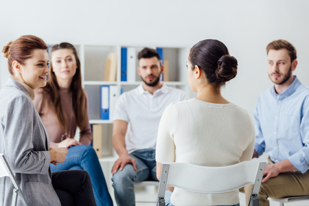 group of people sitting in circle on chairs during support group session