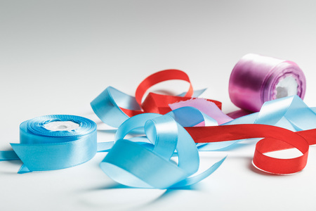 curved blue, red and purple satin ribbons with spools on grey background Stock Photo