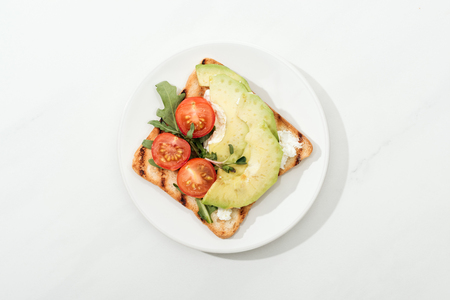 Top view of toast with cherry tomatoes and avocado on plate on white surface