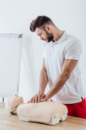 handsome man using chest compression technique on dummy during cpr training