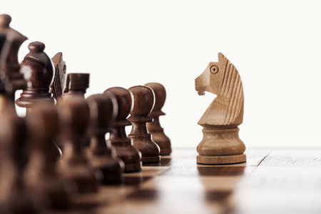 selective focus of wooden chessboard with chess figures and knight in front isolated on white