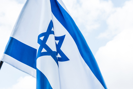 national flag of israel with star of david against sky with clouds Stock Photo