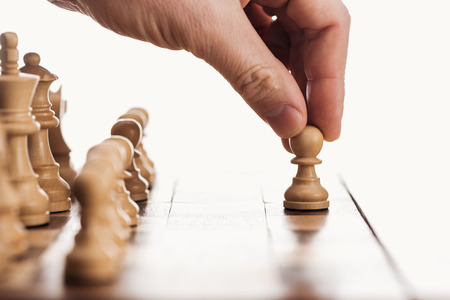 partial view of man doing move with pawn on wooden chessboard isolated on white 写真素材
