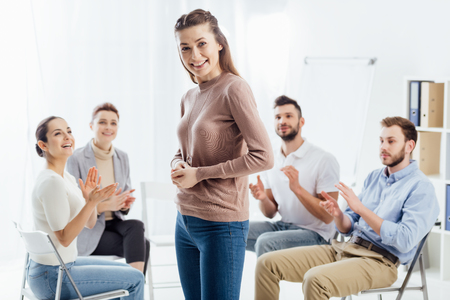 smiling woman looking at camera while people sitting and applauding during group therapy session Reklamní fotografie