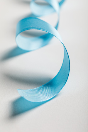 close up of curved blue satin ribbon on grey background Stock Photo