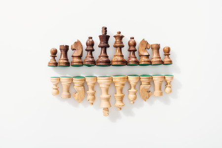 top view of rows made of brown and beige wooden chess figures on white background