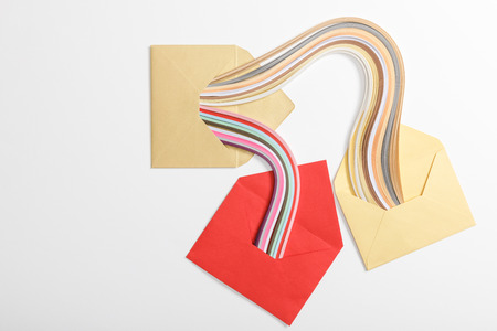 top view of yellow and red envelopes with multicolored rainbow on grey background