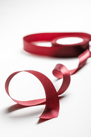 selective focus of silk wavy burgundy ribbon with spool on grey background