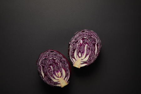Top view of cut red cabbage on black surface