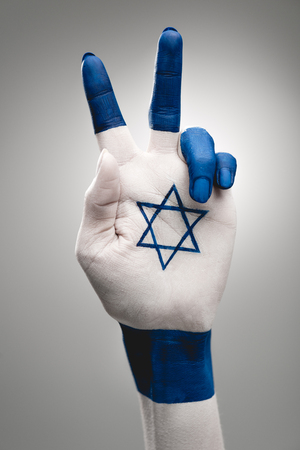 cropped view of female hand with blue star of david showing peace sign on grey