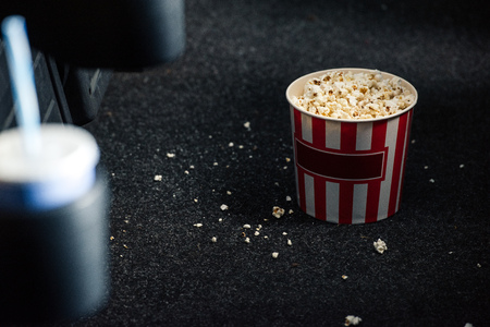 selective focus of stripped red and white paper cup with popcorn on floor