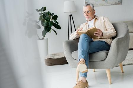 nachdenklicher älterer Mann mit Brille, der ein Buch hält, während er zu Hause im Sessel sitzt