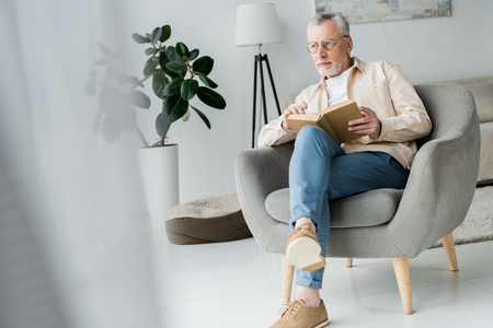 pensive senior man in glasses holding book while sitting in armchair at home