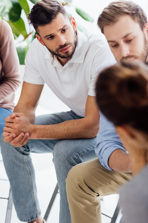 selective focus of men sitting during group therapy session Stock Photo