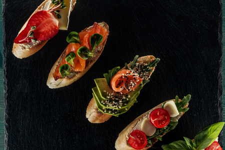 top view of italian bruschetta with salmon, tomatoes and avocado on wooden table