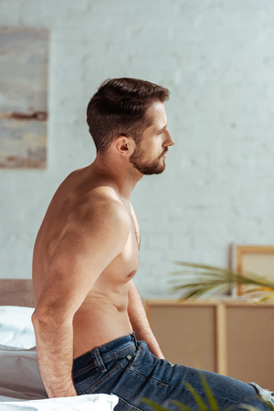 side view of good-looking and muscular man sitting on bed and looking away in bedroom