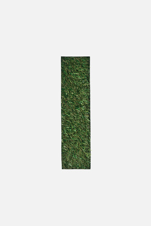 top view of cut out I letter on green grass background isolated on white