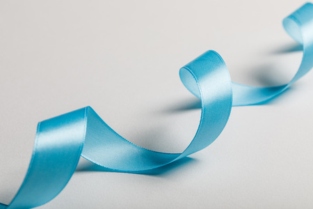 close up of curved blue satin ribbon on grey background 스톡 콘텐츠