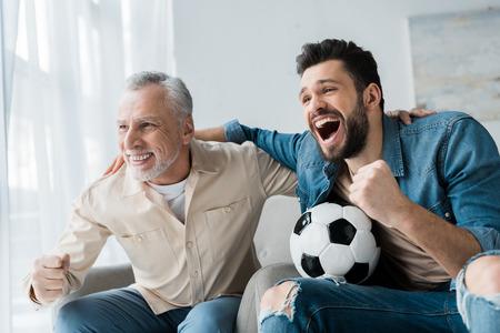 Feliz hombre jubilado viendo campeonato y animando con guapo hijo sosteniendo el fútbol Foto de archivo