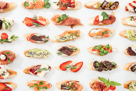background of traditional italian bruschetta with salmon, prosciutto, dried tomatoes, avocado, strawberries and herbs on white Stock Photo