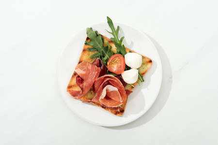 Top view of toast with cherry tomato, arugula and prosciutto on plate on white surface