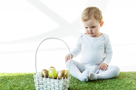 cute baby sitting on green grass near straw basket with traditional Ester eggs isolated on white