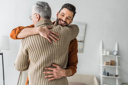 gelukkige bebaarde man die lacht terwijl hij zijn oudere vader thuis knuffelt
